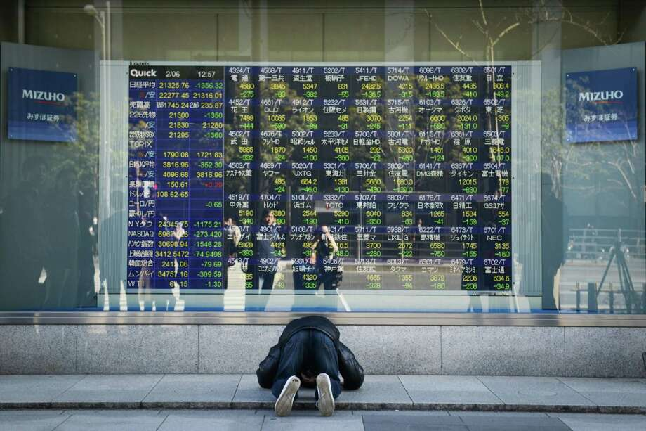 A man looks at an electronic stock board showing a chart of the Nikkei Stock Average outside a securities firm in Tokyo on Feb. 2, 2018. Photo: Bloomberg Photo By Noriko Hayashi. / © 2018 Bloomberg Finance LP
