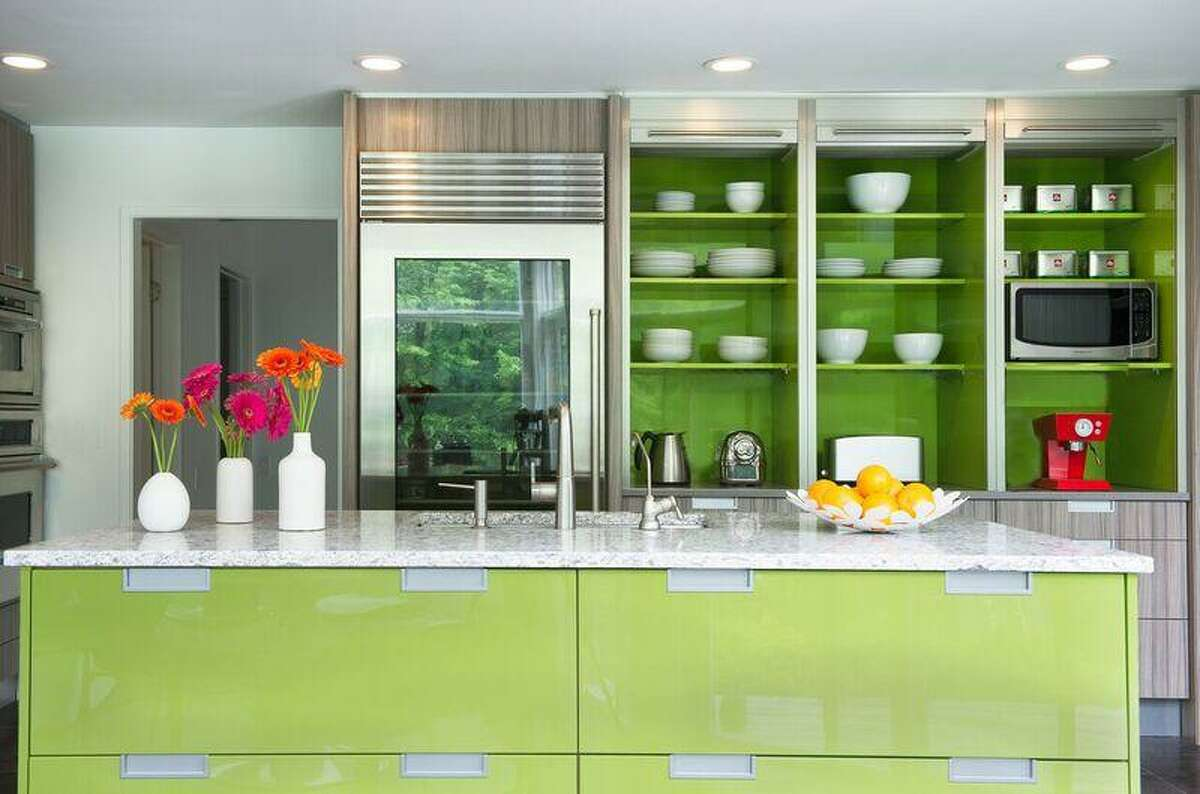 DEANE, Inc., with locations in Stamford and New Canaan, designed this kitchen which features lime green high gloss lacquered cabinetry paired with light rift oak laminate and stainless steel details, creating a perfect backdrop for either all white or bold-colored accessories. Inset finger pull hardware adds a clean, contemporary look on the slab door fronts while stainless steel roller shutters hide small appliances when not in use, keeping work areas tidy.