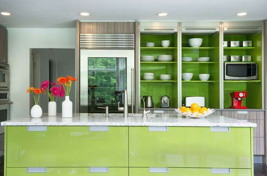 DEANE, Inc., with locations in Stamford and New Canaan, designed this kitchen which features lime green high gloss lacquered cabinetry paired with light rift oak laminate and stainless steel details, creating a perfect backdrop for either all white or bold-colored accessories. Inset finger pull hardware adds a clean, contemporary look on the slab door fronts while stainless steel roller shutters hide small appliances when not in use, keeping work areas tidy. Photo: Jane Beiles / Connecticut Post