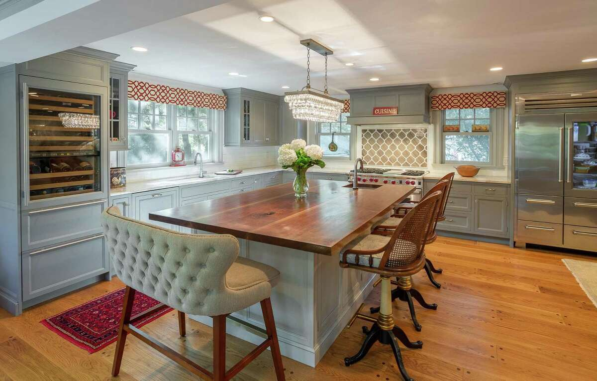 This beautiful traditional style kitchen, designed by Iris Michaels of Karen Berkemeyer Home in Westport, is crafted with inset custom color cabinetry, a mantle wood hood, and stone countertops.