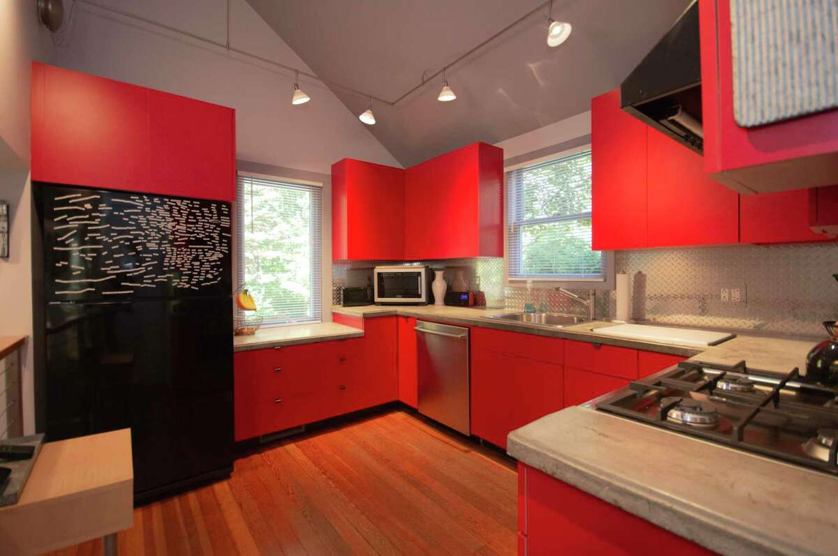 When Michael Neustadt bought his Brookfield home 25 years ago, he was unhappy with the existing white kitchen cabinetry, which he eventually replaced with red cabinets, giving the kitchen its