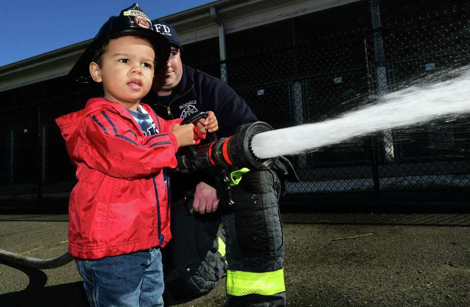 Norwalk firefighter Brian Filush helps Gabriel Wolk of Norwalk, 2, spray the fire hose during The Norwalk Open House and Touch-a-Truck event on Saturday in Norwalk. Photo: Erik Trautmann / Hearst Connecticut Media / Norwalk Hour