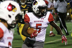 Alton's Tim Johnson (5) heads upfield for some of his 155 rushing yards Friday night in the Redbirds' 41-36 Southwestern Conference football victory in O'Fallon.