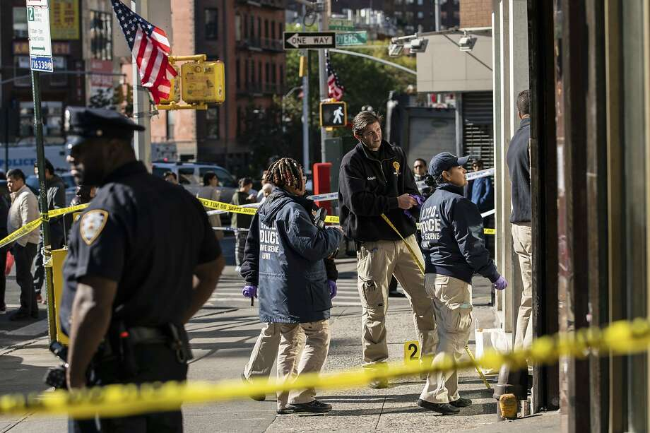 New York Police Department officers investigate the scene of an attack in Manhattan's Chinatown neighborhood, Saturday, Oct. 5, 2019 in New York. Four men who are believed to be homeless were attacked and killed early Saturday in a street rampage. NYPD Detective Annette Shelton said that a fifth man remained in critical condition after also being struck with a long metal object that authorities recovered. (AP Photo/Jeenah Moon) Photo: Jeenah Moon, Associated Press