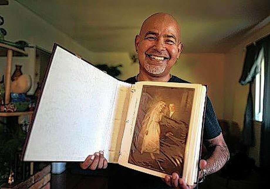 San Antonian Mike Rodriguez bought this photo album for $8 in a flea market. The album has family photos dating back to the 1800s, and Rodriguez was able to track down some of the people in the pictures to Illinois. Photo: Billy Calzada | Express-News (AP)