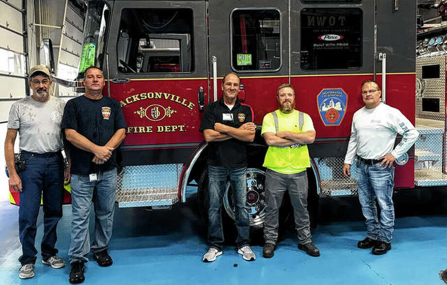 John Cooper (from left), the head mechanic for Jacksonville; Fire Captain Mike Martin; Fire Chief Doug Sills; Scott Mumford and Fire Captain Brian Nyberg view the city's new fire trucks at the Pierce Manufacturing factory in Wisconsin. Photo: Photo Provide By Doug Sills