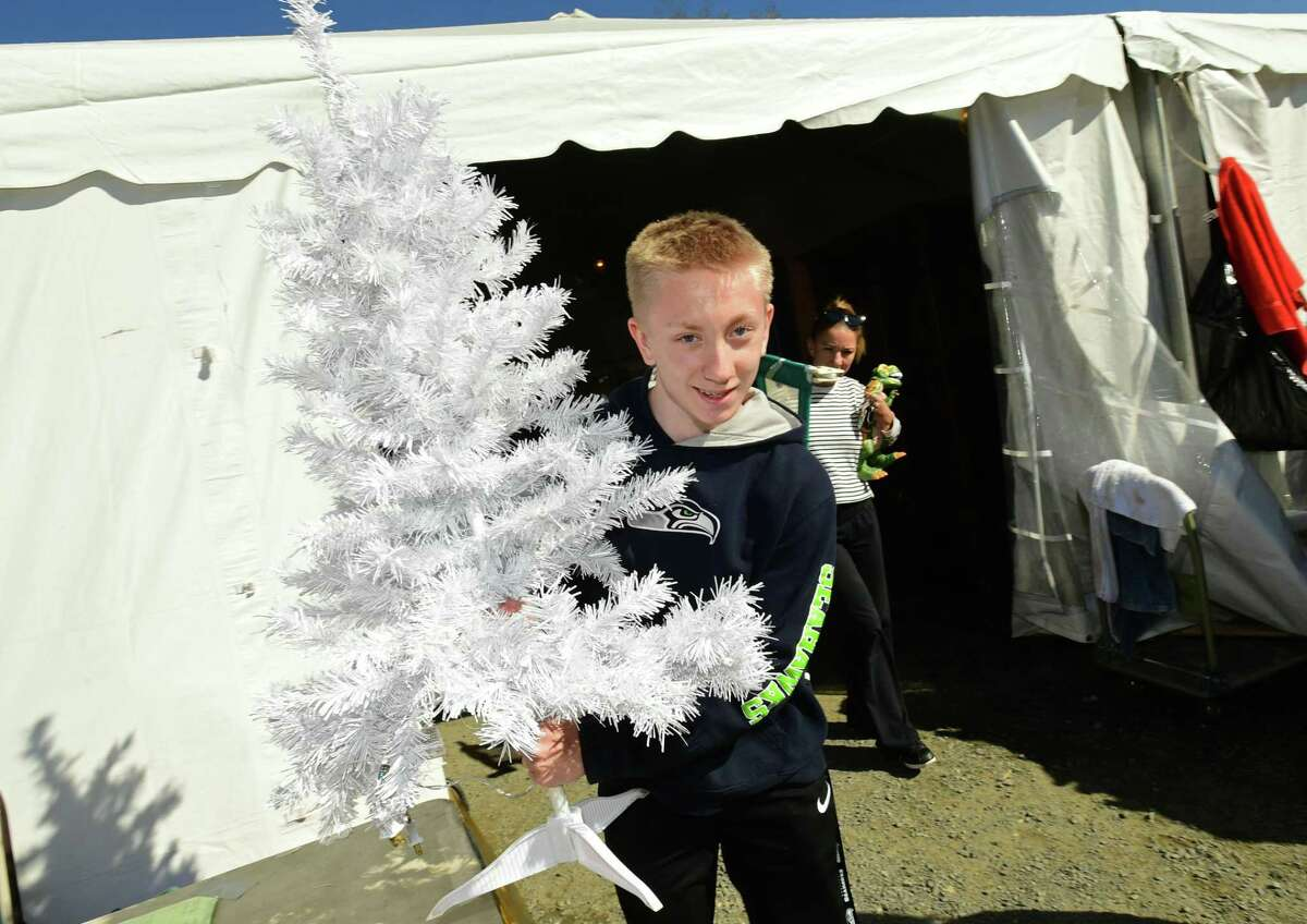 Kyle Young of Norwalk buys a Christmas tree at the Fall 2019 Minks to Sinks tag sale.