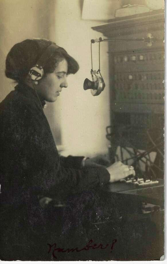 """Postcard photo showing """"Mrs. Link of S. Benzonia"""" at work in the Benzonia telephone office; upstairs in the Benzonia Bank building, later Dr. Wagner's veterinary office. (Courtesy Photo)"""