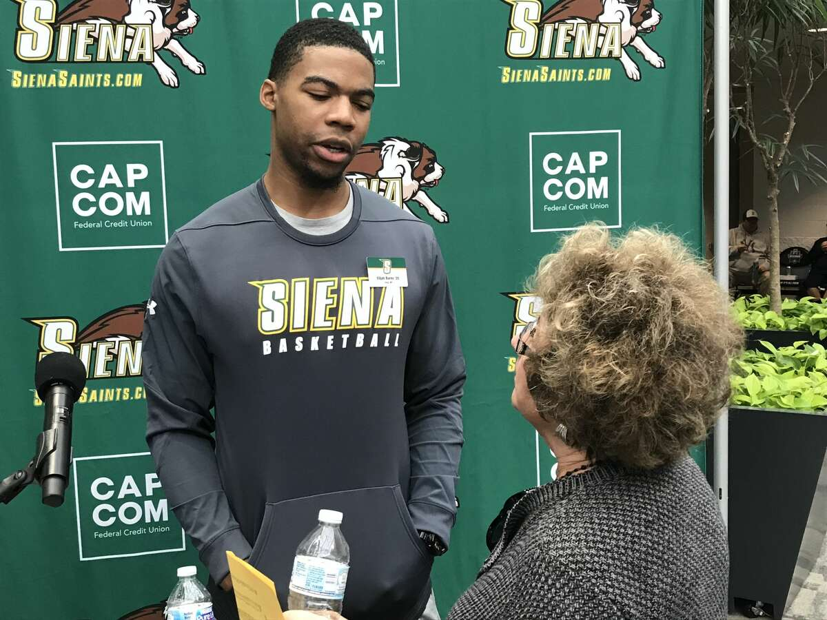 Siena graduate forward Elijah Burns of Troy speaks with a fan at the
