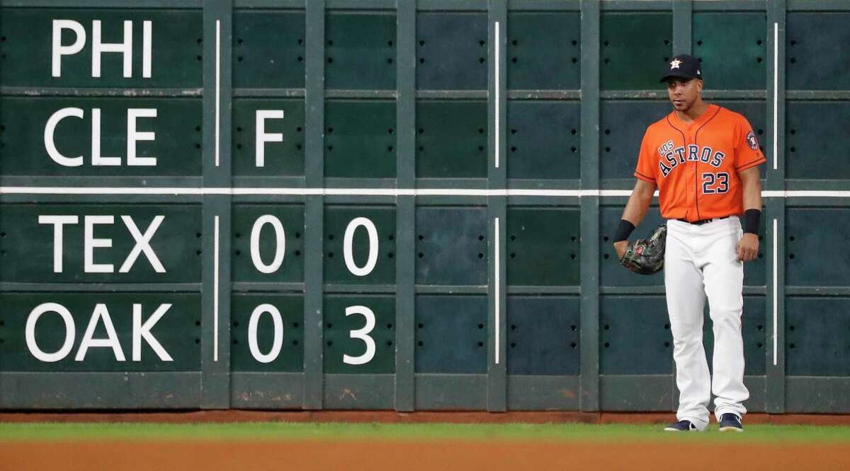 Houston Astros left fielder Michael Brantley (23) stands near the scoreboard showing the score of the Rangers-Oakland A's game during the ninth inning of an MLB baseball game at Minute Maid Park, Friday, Sept. 20, 2019, in Houston.