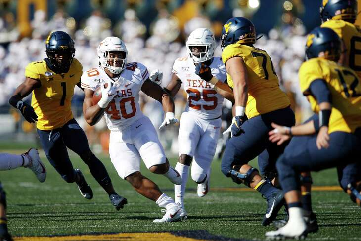 MORGANTOWN, WV - OCTOBER 05: Ayodele Adeoye #40 of the Texas Longhorns runs with the ball after intercepting a pass in the first quarter against the West Virginia Mountaineers at Mountaineer Field on October 5, 2019 in Morgantown, West Virginia.
