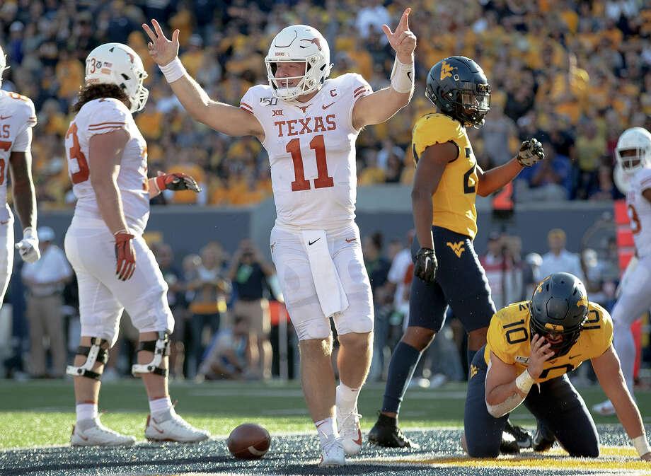 Texas quarterback Sam Ehlinger (11) celebrates a touchdown against West Virginia during an NCAA college football game on Saturday, Oct. 5, 2019, in Morgantown, W.Va. (Nick Wagner/Austin American-Statesman via AP) Photo: Nick Wagner, Associated Press / Austin American-Statesman