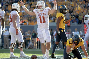 Texas quarterback Sam Ehlinger (11) celebrates a touchdown against West Virginia during an NCAA college football game on Saturday, Oct. 5, 2019, in Morgantown, W.Va. (Nick Wagner/Austin American-Statesman via AP)