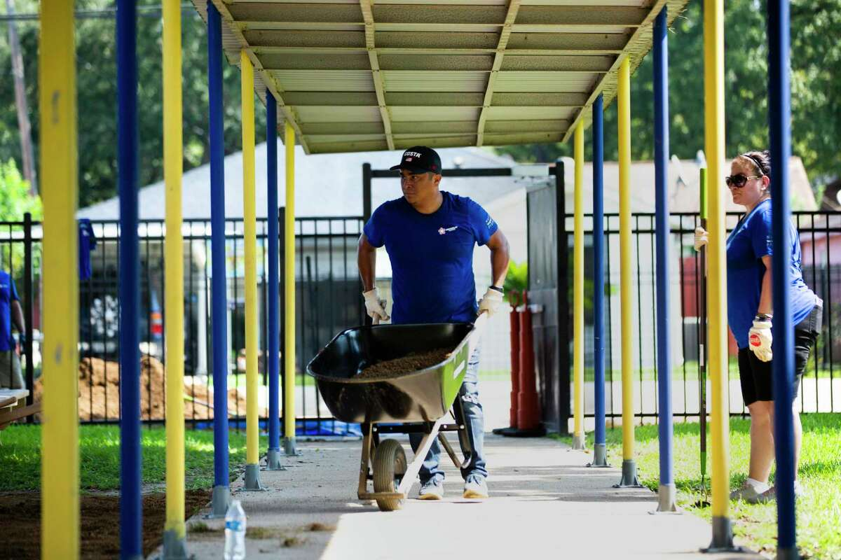 Chris Garcia, a Republic Services supervisor carries dirt to build a playground for the students of Adele B. Looscan Elementary School on Saturday, Oct. 5, 2019.