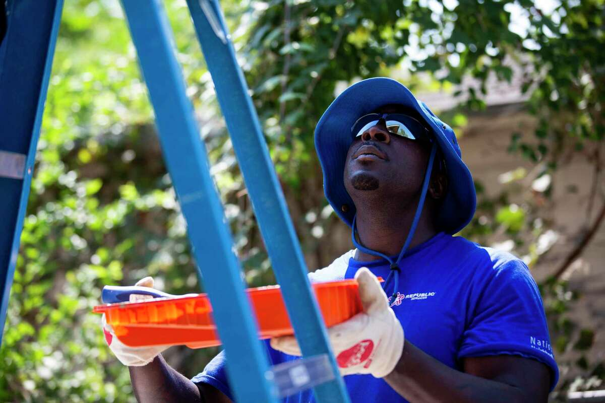 Michael Davis a Republic Services employee holds house paint while volunteering with colleagues in the north side of Houston on Saturday, Oct. 5, 2019. Over 100 employees joined forces to repair several homes and the yard of a school.