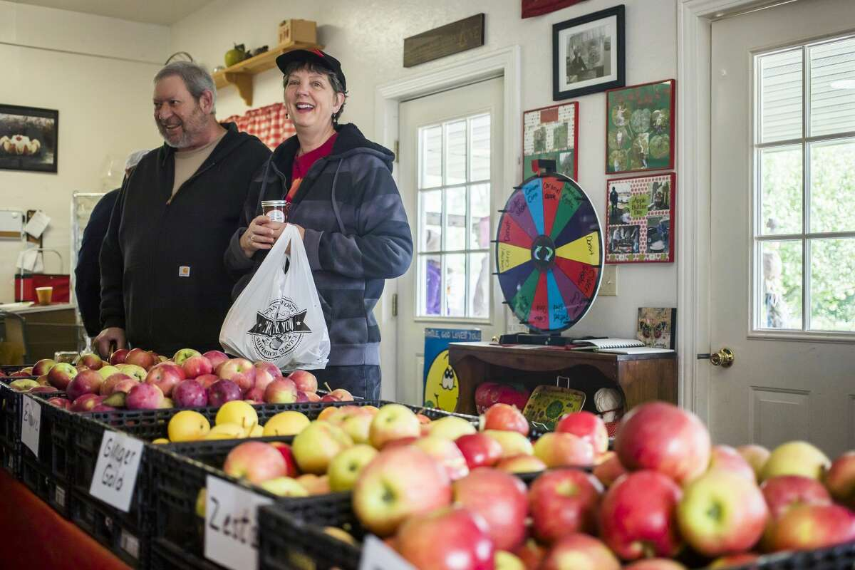 Rick and Kelly Reger of Sanford check out the wide variety of apples available inside the store during Apple Butter Day Saturday, Oct. 5, 2019 at Apple Blossom Orchard. (Katy Kildee/kkildee@mdn.net)