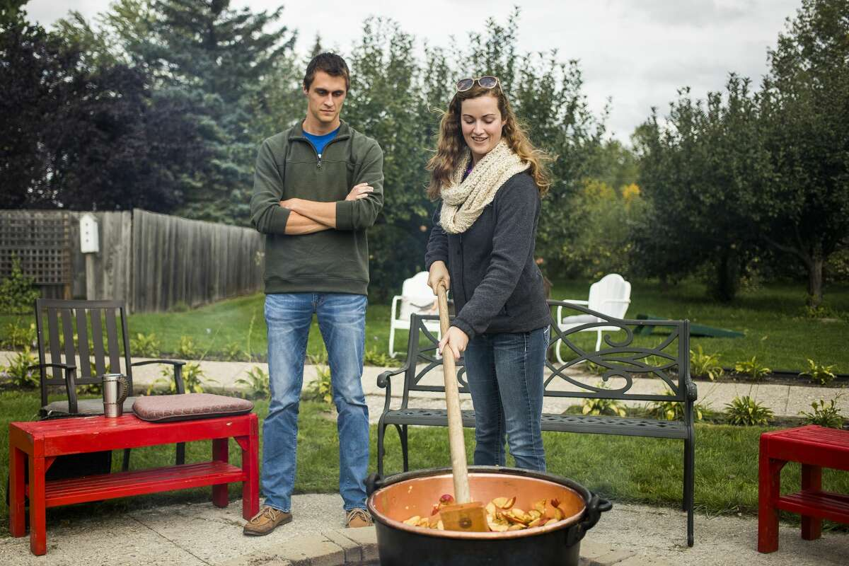 Megan Rabbers of Saginaw, right, stirs a pot of sliced apples which will eventually be made into apple butter as Jason Spaude of Saginaw watches during Apple Butter Day Saturday, Oct. 5, 2019 at Apple Blossom Orchard. (Katy Kildee/kkildee@mdn.net)