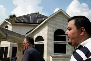 Jose Flores, right, gives a solar power tour of his home on Saturday, Oct. 5, 2019, in Clear Creek. Flores has 46 solar panels and two Tesla powerwalls.