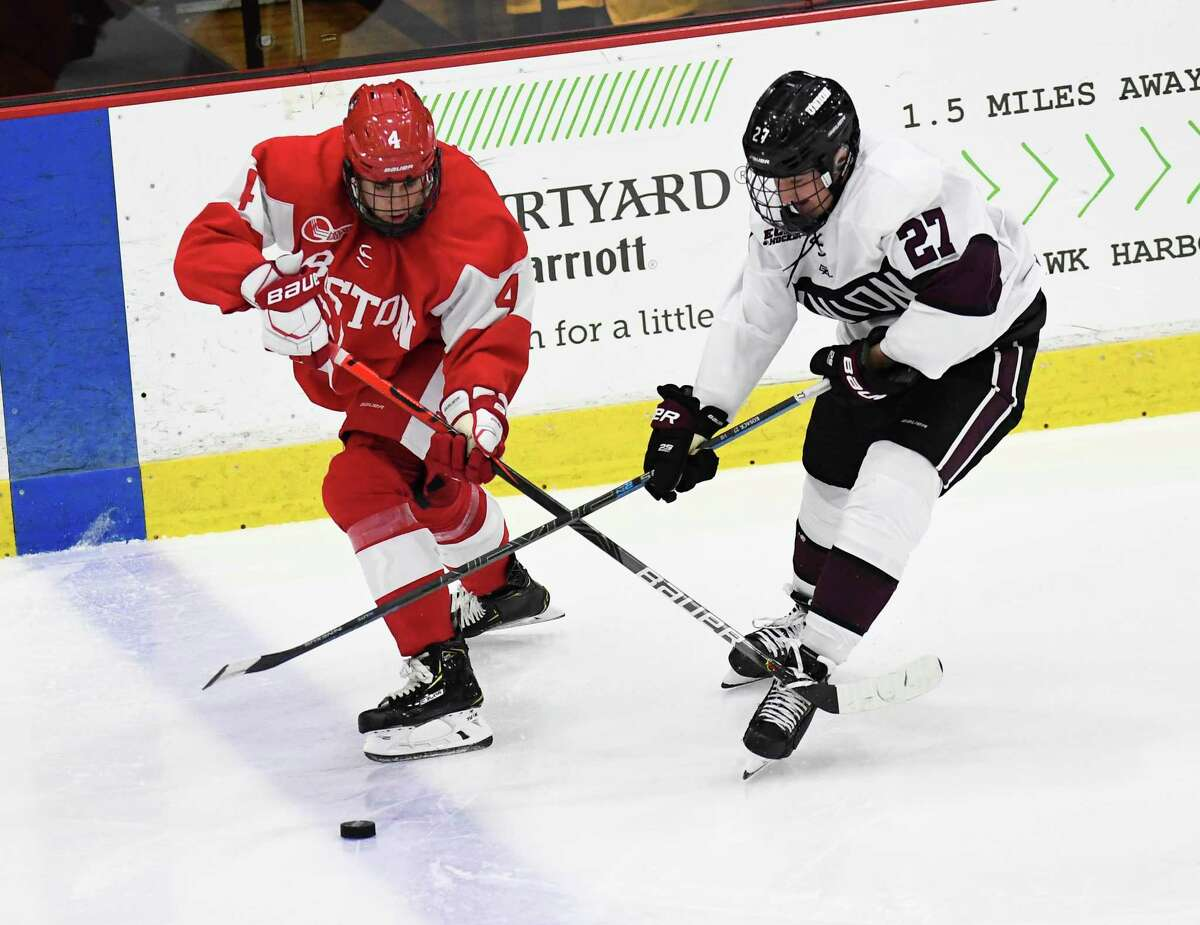 Boston University defenseman David Farrance (4) and Union forward Sebastian Vidmar (27) chase the puck during the second period of an NCAA college Hockey home opener game Saturday, Oct. 5, 2019, in Schenectady, N.Y.