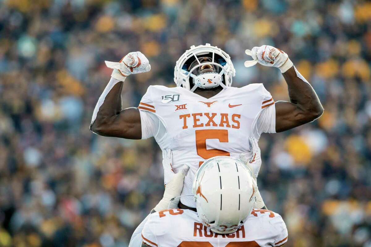 Texas defensive back D'Shawn Jamison (5) and defensive lineman Malcolm Roach (32) celebrate after Jamison intercepted a pass during the second half of an NCAA college football game against West Virginia, Saturday, Oct. 5, 2019, in Morgantown, W.Va. (AP Photo/Raymond Thompson)