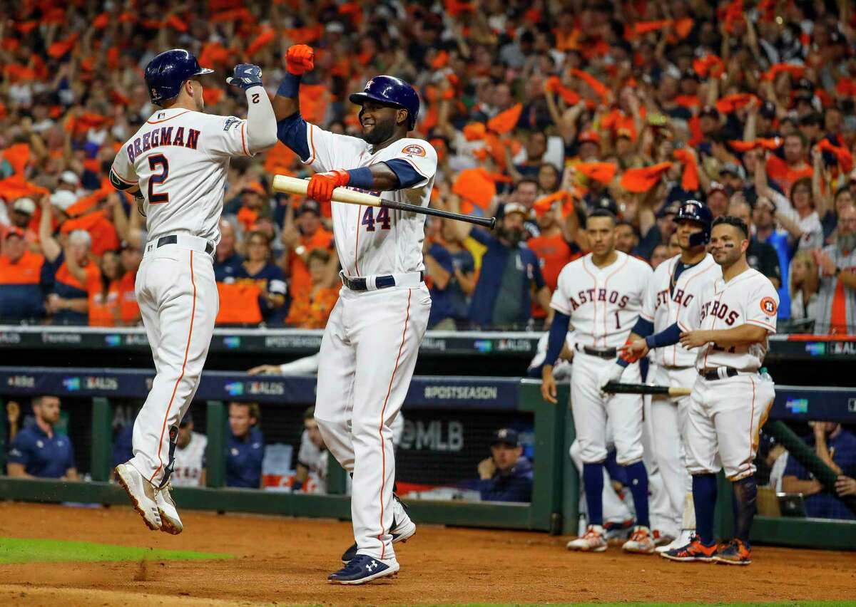 Houston Astros third baseman Alex Bregman (2) is welcomed back to the dugout by Houston Astros designated hitter Yordan Alvarez (44) after hitting a home run during the fourth inning of Game 2 of the American League Division Series at Minute Maid Park on Saturday, Oct. 5, 2019, in Houston.