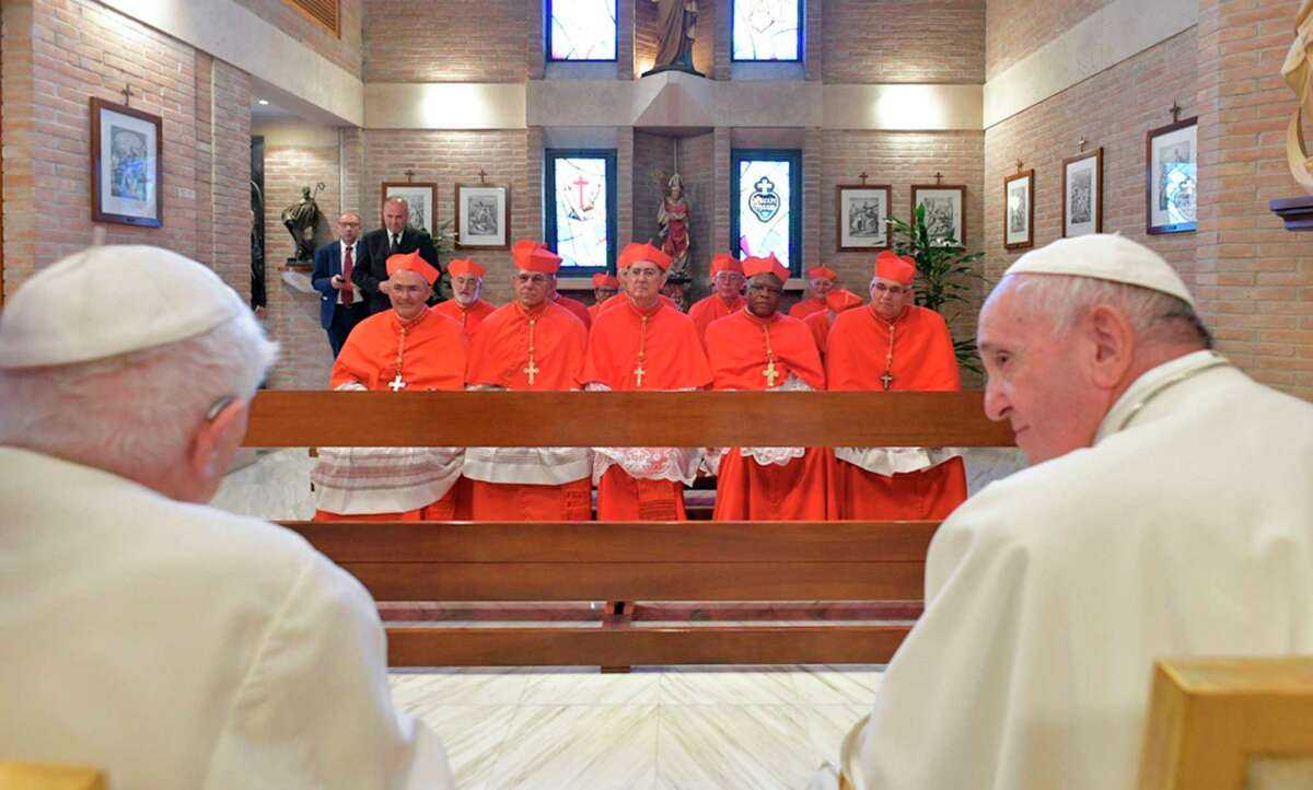 """This photo taken and handout by The Vatican Media on October 5, 2019 shows Pope Francis (Front R) and former Pope Benedict XVI (Front L) meeting with Italian Cardinal Eugenio Dal Corso, Canadian Cardinal Michael Czerny, English Cardinal Michael Louis Fitzgerald, Indonesian Cardinal Ignatius Suharyo Hardjoatmodjo, Guatemalan Cardinal Alvaro Leonel Ramazzini Imeri, Cuban prelate Juan de la Caridad Garcia Rodriguez, Spanish Cardinal Miguel Angel Ayuso Guixot, Portuguese Cardinal Jose Tolentino Mendonca, Italian Cardinal Matteo Maria Zuppi, Spanish prelate Cristobal Lopez Romero, Lithuanian Cardinal Sigitas Tamkevicius, Congolese Cardinal Fridolin Ambongo Besungu and Luxembourgish prelate Jean-Claude Hollerich, the 13 prelates Pope Francis appointed Cardinals during an Ordinary Public Consistory for the creation of new cardinals at St. Peter's Basilica in the Vatican. - Pope Francis appoints 13 new cardinals at the 2019 Ordinary Public Consistory, choosing prelates whose lifelong careers reflect their commitment to serve the marginalized and local church communities, hailing from 11 different nations and representing multiple religious orders. (Photo by Handout / VATICAN MEDIA / AFP) / RESTRICTED TO EDITORIAL USE - MANDATORY CREDIT """"AFP PHOTO / VATICAN MEDIA"""" - NO MARKETING - NO ADVERTISING CAMPAIGNS - DISTRIBUTED AS A SERVICE TO CLIENTS (Photo by HANDOUT/VATICAN MEDIA/AFP via Getty Images)"""