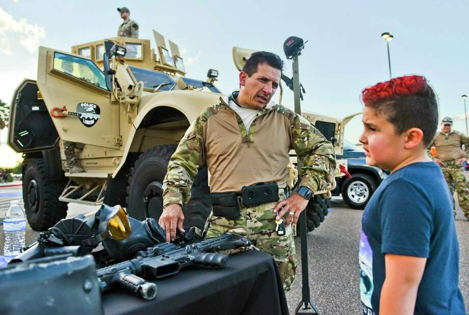 Jorge Martinez, left, speaks Tuesday with Geronimo Gonzalez about the guns and protection used by Laredo Police during the National Night Out Law Enforcement Expo at Sames Auto Arena. Photo: Danny Zaragoza /Laredo Morning Times / Laredo Morning Times