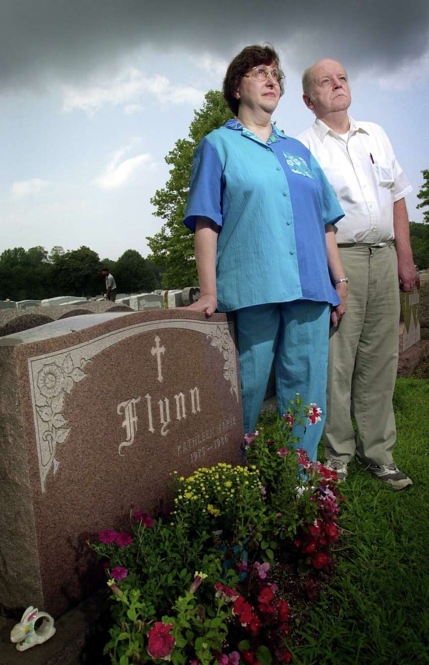 FILE - Esther and Jim Flynn, parents of Kathleen Marie Flynn who was raped and murdered in 1986 while walking home from school, at her grave at St. John's cemetery.