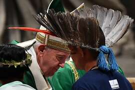 Representatives of one of the Amazon Rainforest's ethnic groups (Front) take part in Pope Francis' (L) mass on October 6, 2019 at St. Peter's Basilica in the Vatican, for the opening of the Special Assembly of the Synod of Bishops for the Pan-Amazon Region. - Pope Francis will gather Catholic bishops at the Vatican on October 6 to champion the isolated and poverty-struck indigenous communities of the Amazon, whose way of life is under threat. (Photo by Tiziana FABI / AFP) (Photo by TIZIANA FABI/AFP via Getty Images)