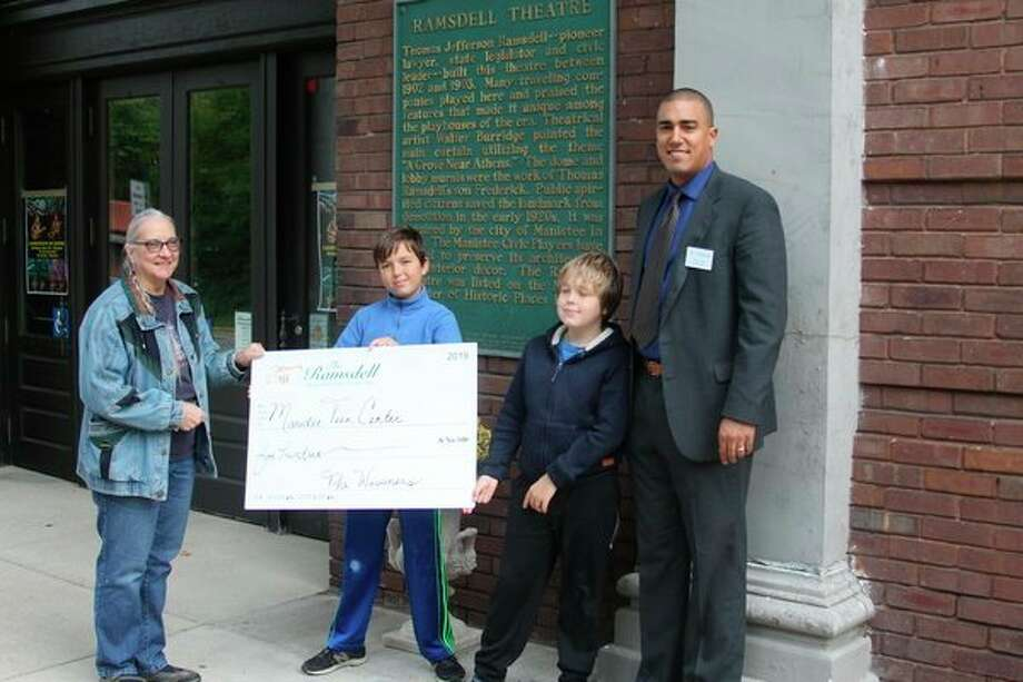 Manistee Teen Center director Shiela Kaminski (left) accepts a check from Michael Sager Wissner and Anthony Sager Wissner for $500 that was raised from their family magic show at the Ramsdell Theatre in August as Ramsdell Regional Center for the Arts Xaiver Verna (right) looks on. (Ken Grabowski/News Advocate)