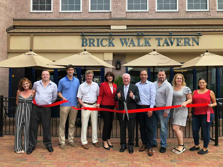 First Selectman Mike Tetreau cuts the ribbon as the Brick Walk Tavern celebrates its first anniversary. Photo: Contributed Photo