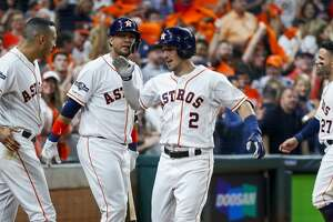 Houston Astros third baseman Alex Bregman (2) is welcomed back to the dugout by shortstop Carlos Correa (1) and first baseman Yuli Gurriel (10) after hitting a home run during the fourth inning of Game 2 of the American League Division Series at Minute Maid Park on Saturday, Oct. 5, 2019, in Houston.