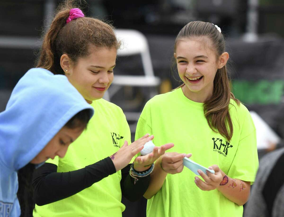 Kids Helping Kids participants Olivia Stiebel, left, 12, and Chloe Gerace, 13, play with putty during the Stamford Public Education Foundation (SPEF) US Day 2019 at Mill River Park in Stamford, Conn. Sunday, Oct. 6, 2019. The day kicked off with the 7th Annual MarcUS for Change 5K Walk & Run and awards presentation. Following the race was the 6th Annual STEMfest, featuring about 40 STEM-related displays and experiments. The Mayor's MultiCultural Council's International Dance Festival entertained the crowd with a variety of unique cultural dances.