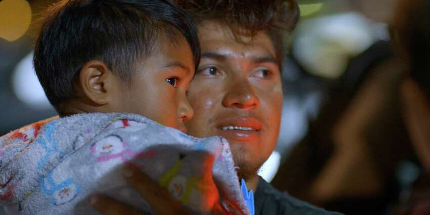 This image released by Netflix shows Luis Diaz, a migrant from Honduras who is living in the U.S. illegally, holding his son Noah in Kansas City, Mo., before the child and his mother are deported in a scene from the six-episode docuseries