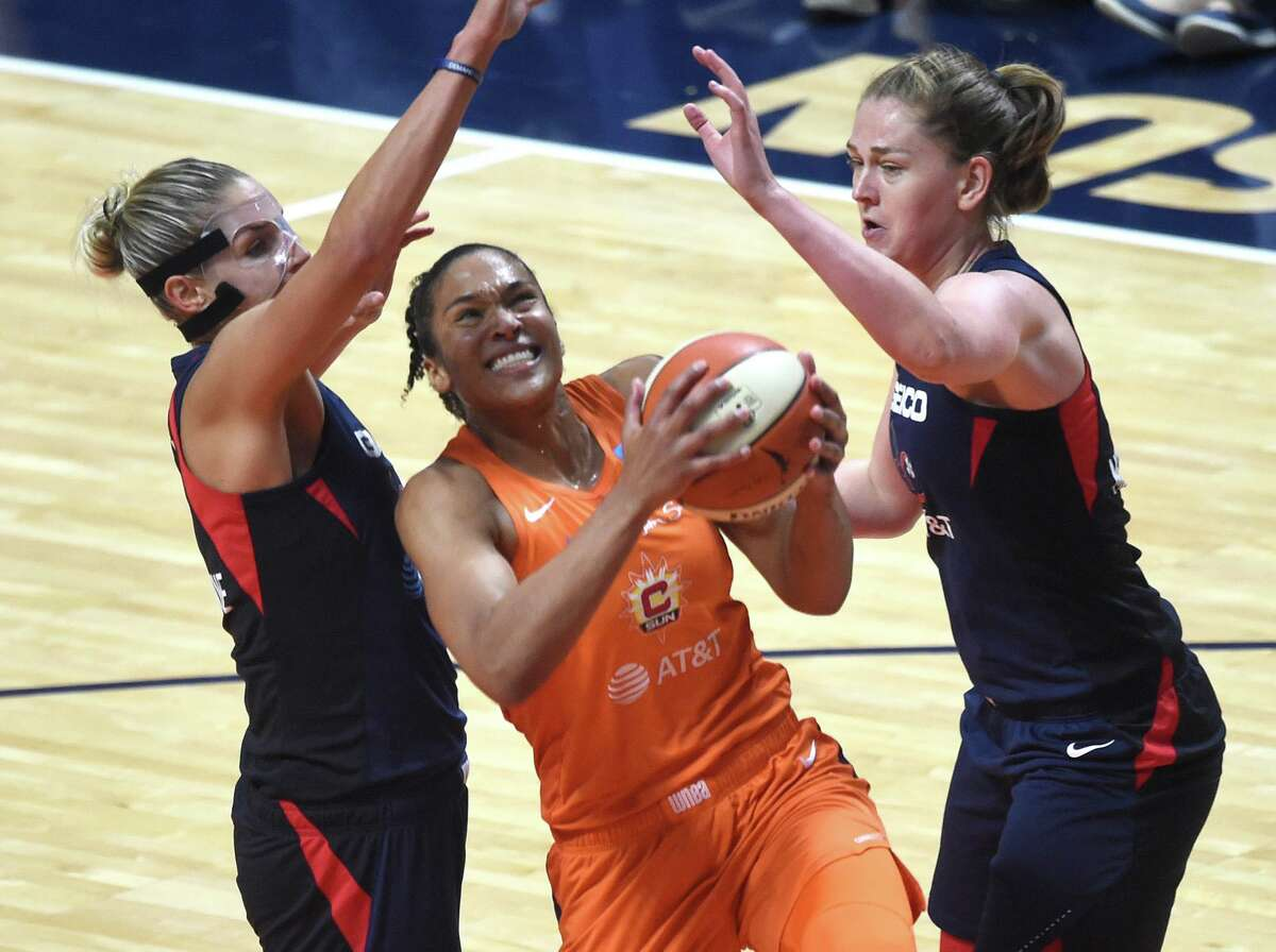 Connecticut Sun forward Alyssa Thomas goes to the basket between Washington Mystics forwards Elena Delle Donne, left, and Emma Messeman in Game 3 of the WNBA Finals on Sunday, Oct. 6, 2019, at Mohegan Sun Arena in Uncasville. Washington won the game 94-81.
