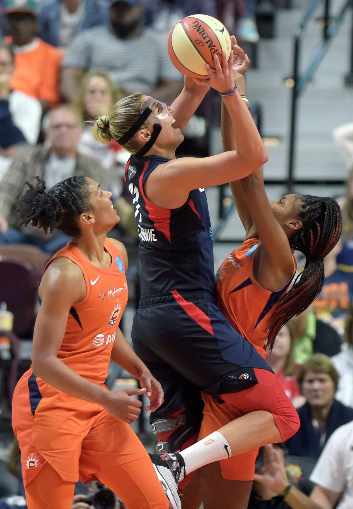 Washington Mystics forward Elena Delle Donne, center, goes to the basket between Connecticut Sun players Alyssa Thomas, left, and Bria Holmes in Game 3 of the WNBA Finals on Sunday, Oct. 6, 2019, at Mohegan Sun Arena in Uncasville. Washington won the game 94-81.