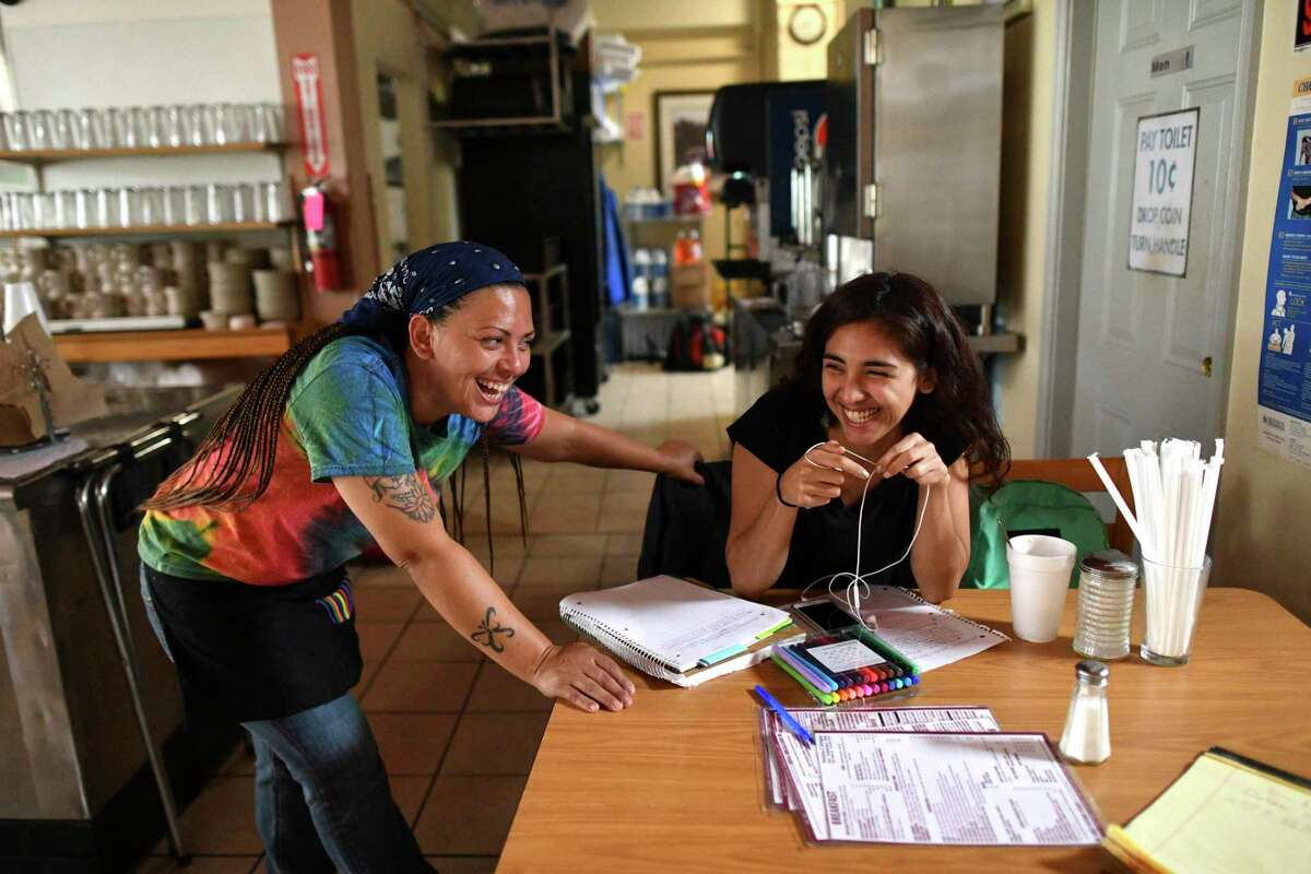 Waitress Krystal Torres encourages her daughter, Daizie Saldaña, who does her homework as she waits for her mother to finish her shift at Panchos & Gringos on Friday, June 21, 2019. Torres no longer works at the restaurant, but customers still remember her friendly, caring attitude.