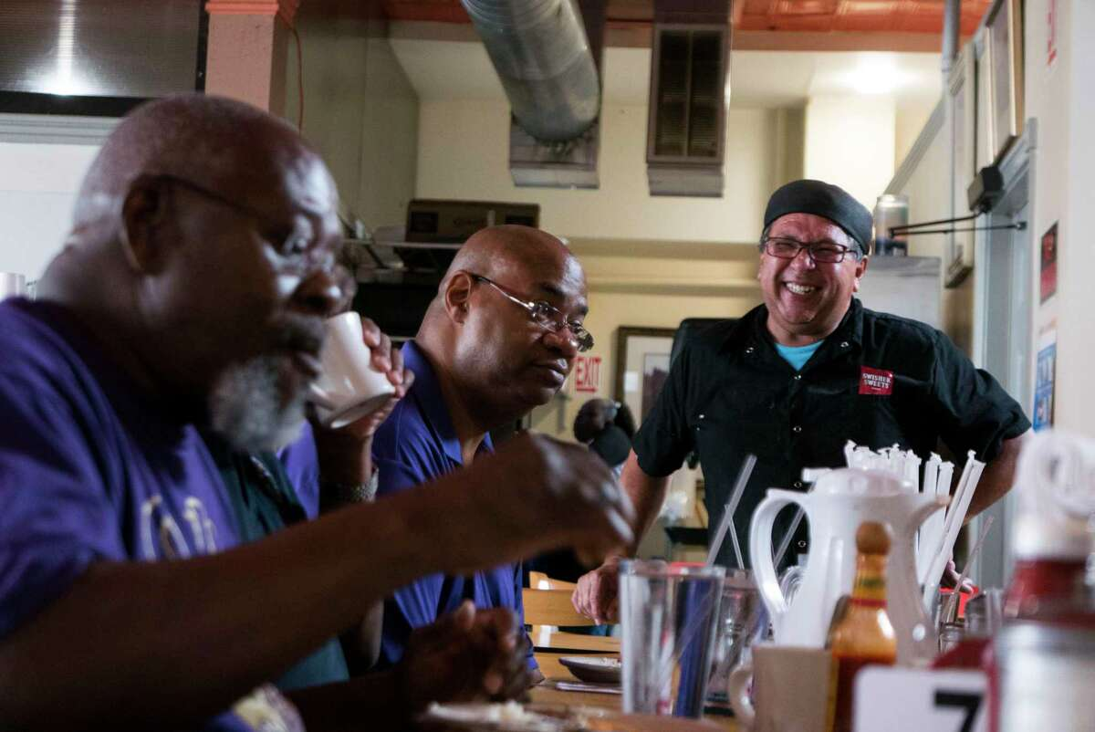 Sergio Calderon, chef and owner of Panchos & Gringos, chats with customers Herbert Nance, left, and Charles Whittaker. The restaurant has become the heart of its East Side neighborhood.