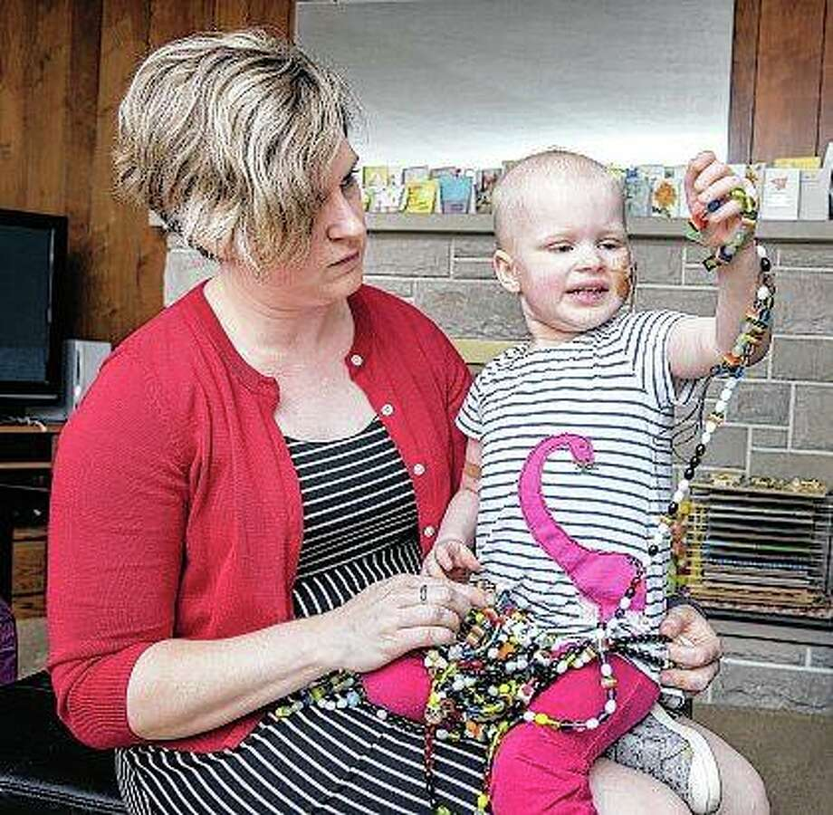 Jenny Abbott holds her 3-year-old daughter, Elizabeth, at their home in Urbana. Elizabeth, who has leukemia, has received 850 artist-made beads through Ann & Robert H. Lurie Children's Hospital of Chicago, where she's gone for care. Photo: Rick Danzl | The News-Gazette (AP)