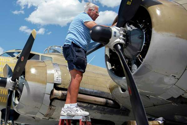 "In This July 1, 2019 photo, Ernest ""Mac"" McCauley, a veteran pilot who volunteers with the Collings Foundation, works on one of the nine-cylinder radial engines on a B-17 Flying Fortress bomber on display at the Spokane International Airport in Spokane, Wash. McCauley, 75, of Long Beach, Calif., and his co-pilot were among seven people killed when the bomber crashed and burned Wednesday, Oct. 2, at Bradley International Airport in Windsor Locks, Conn."