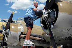 """FILE - In this July 1, 2019 photo, Ernest """"Mac"""" McCauley, a veteran pilot who volunteers with the Collings Foundation, works on one of the nine-cylinder radial engines on a B-17 Flying Fortress bomber on display at the Spokane International Airport in Spokane, Wash. McCauley, 75, of Long Beach, Calif., and his co-pilot were among seven people killed when the bomber crashed and burned Wednesday, Oct. 2, 2019, at Bradley International Airport in Windsor Locks, Conn."""