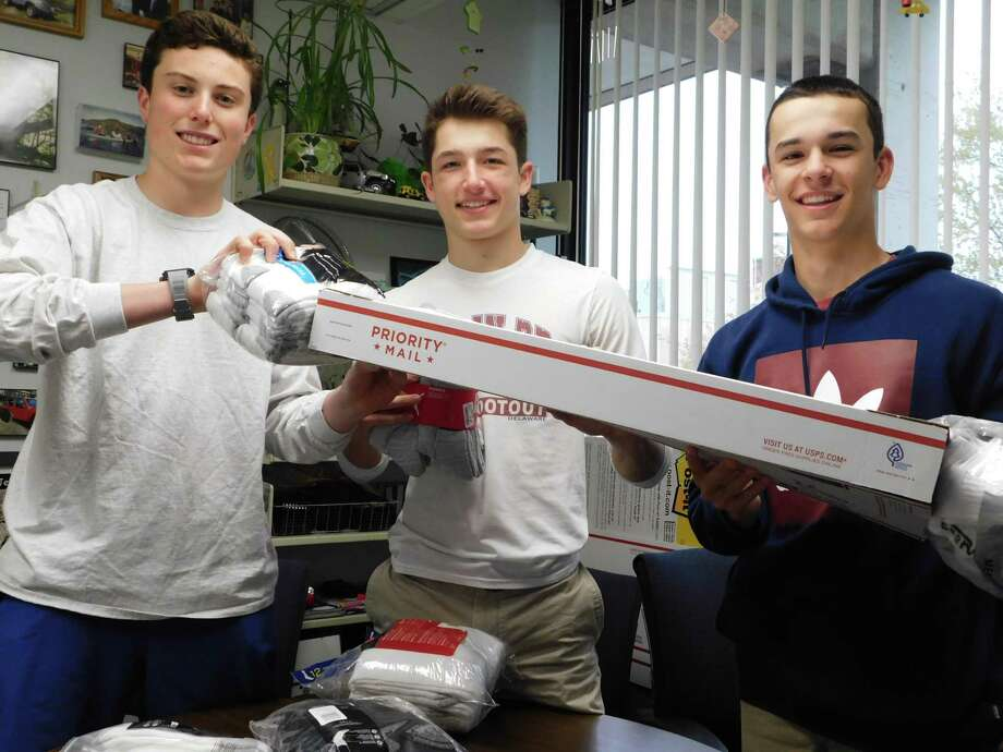 From left, Jack Savarese, Jake Zeyher and Connor Burke prepare to mail a package of socks for Wilton High School's Socks for Soldiers campaign. Photo: Contributed Photo / Wilton High School / Wilton Bulletin Contributed