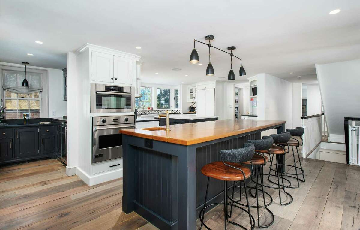 A blue island and lower cabinets offer a fun pop of color in the gourmet kitchen, which also features industrial farmhouse style elements, such as the counter stools and lighting.