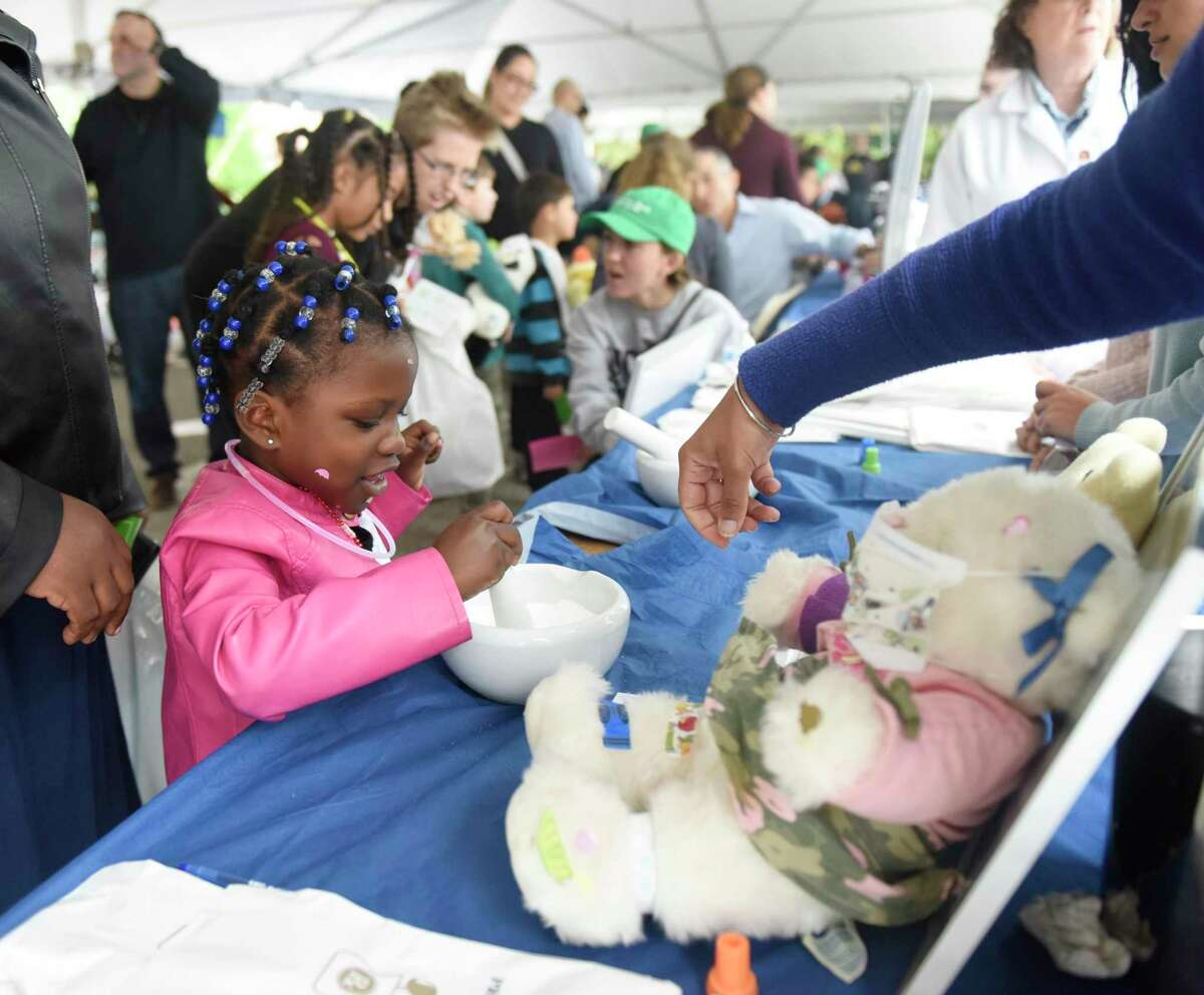 """Davina Duffus, 4, of Bronx, N.Y., prepares a prescription in the """"pharmacy"""" at the Teddy Bear Clinic at Greenwich Hospital in Greenwich, Conn. Sunday, Oct. 6, 2019. The event is staged a mini-hopsital where kids can take their teddy bears through different medical procedures including anesthesia, X-rays, surgery, stitches and more. Greenwich Hospital doctors, nurses and techs were on hand to explain procedures and take the fear out of going to the hopsital for children."""
