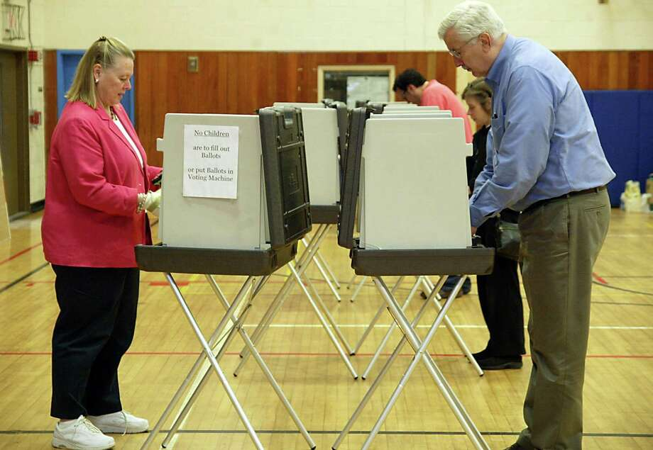(L-R) Ellen Uzenoff and her husband Bob vote, Thurs., April 15, 2010, on the Weston referendum at Weston Middle School. Photo: Phil Noel / ST / Connecticut Post