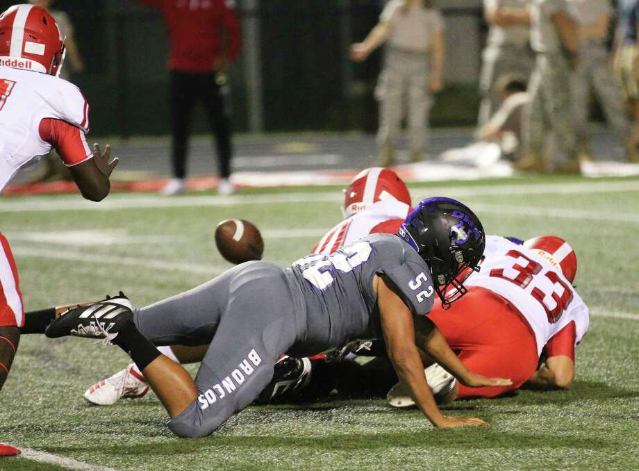 At the bottom of the pile of players is Dayton quarterback Christian Olige who fumbled the ball (left). The Cougars recovered at the Dayton 3-yard line and scored on the next play. Photo: David Taylor / Staff Photo
