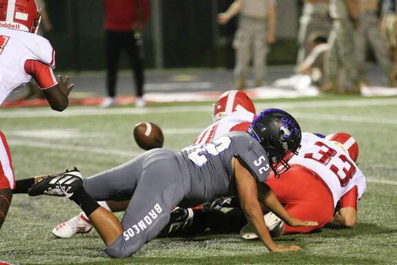 At the bottom of the pile of players is Dayton quarterback Christian Olige who fumbled the ball (left). The Cougars recovered at the Dayton 3-yard line and scored on the next play.