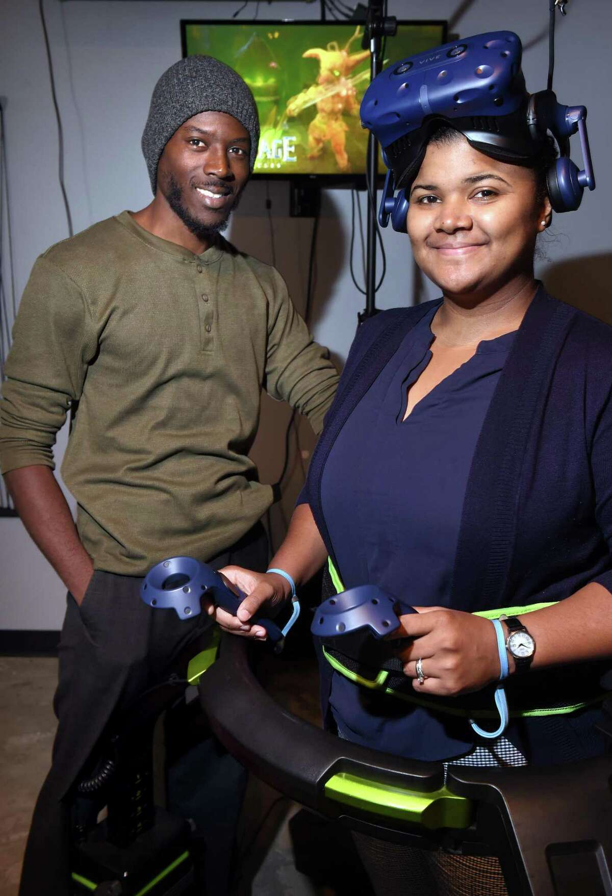 Joseph Champagne, left, and Marileydi Dorival of The Spot VR Lounge are photographed by one of two Virtuix Omni omnidirectional treadmill simulators at the lounge in Orange. Not pictured is Marileydi's husband, co-owner Darison Dorival.