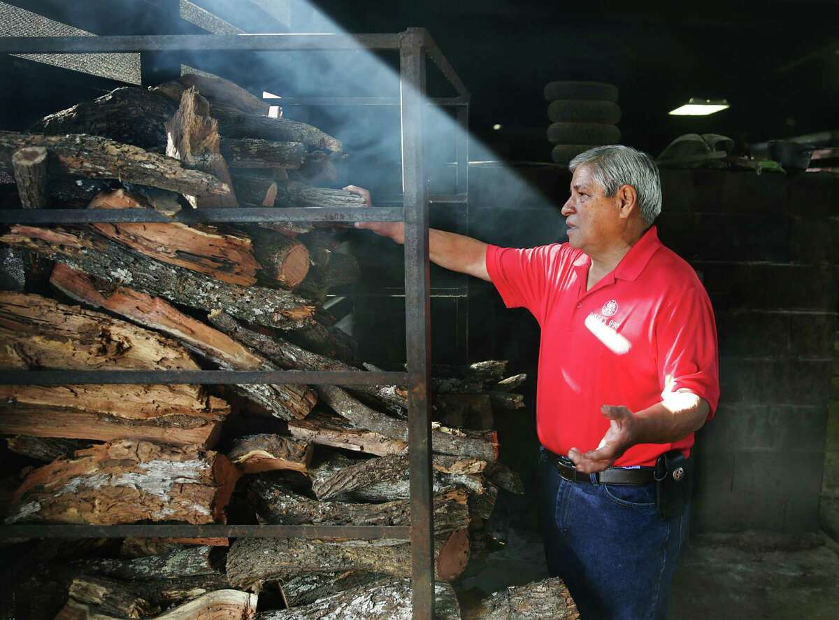 Edward Davila pulls a log of mesquite wood for the pit at Davila's BBQ in Seguin. The restaurant has used mesquite since it first opened 60 years ago.