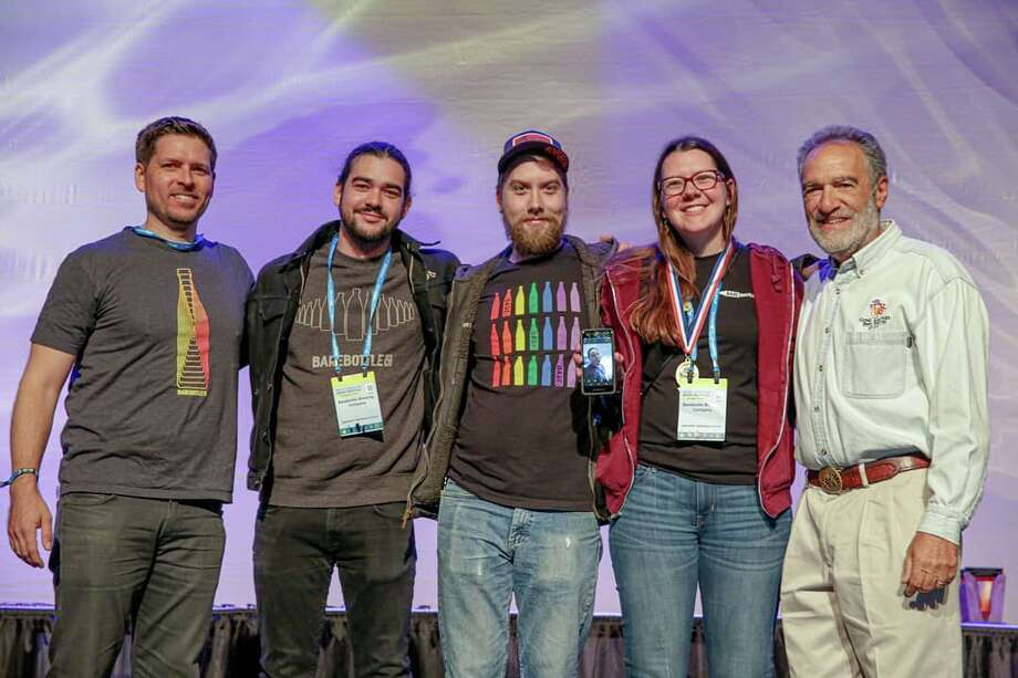 Great American Beer Festival founder Charlie Papazian (R) poses with Barebottle Brewing Company staffers at the Great American Beer festival on Saturday, October 5, 2019. Photo: Barebottle Brewing Company